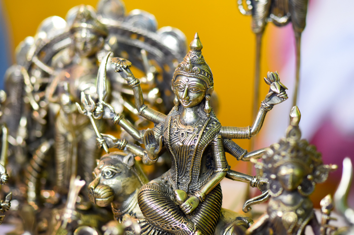 Durga, the goddess of Victory, stands powerful amidst other brass figurines