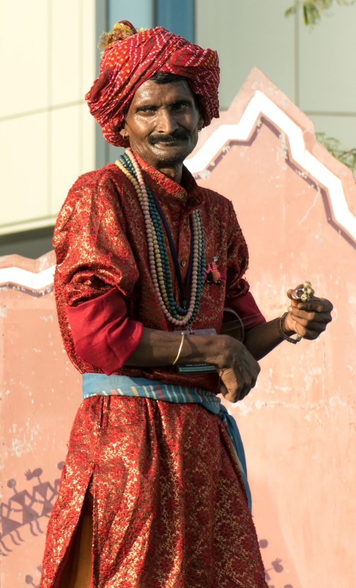 A Rajasthani Artist entertains the crowd with music from handmade stringed musical instruments.