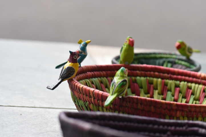 Parrots perched on handmade baskets